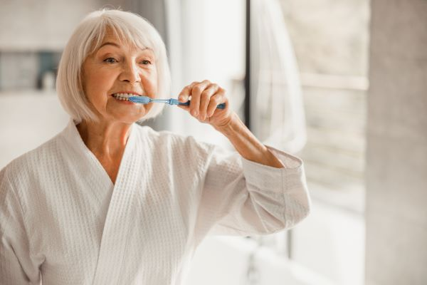 An older woman stands in front of a bathroom mirror and brushes her teeth