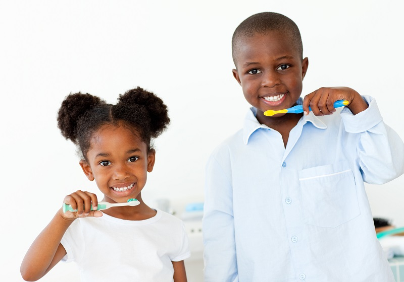 Two childhood siblings smiling and holding toothbrushes with toothpaste up to their mouths
