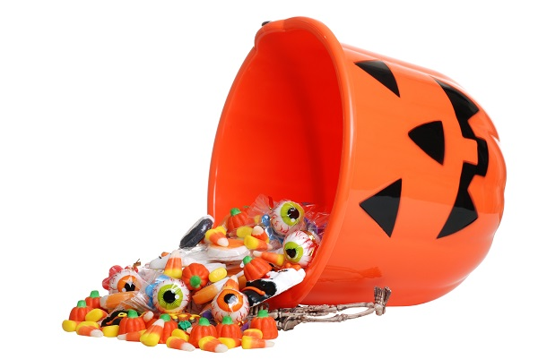 An upturned plastic pumpkin basket with candy spilling out