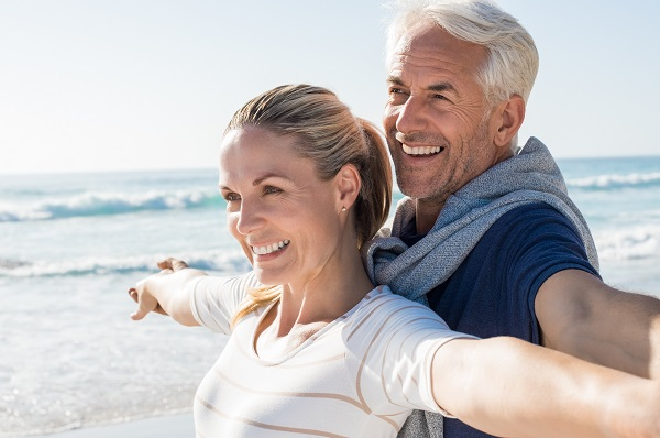 Couple on the beach smiling with implant-supported dentures from Rochester NY