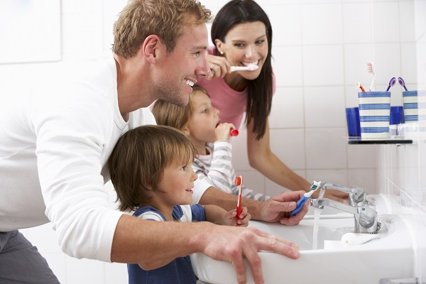 A family of four brushing their teeth in front of the bathroom mirror