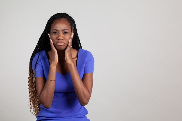 A young woman in a blue shirt holds her hands to her jaw joints because of TMJ pain
