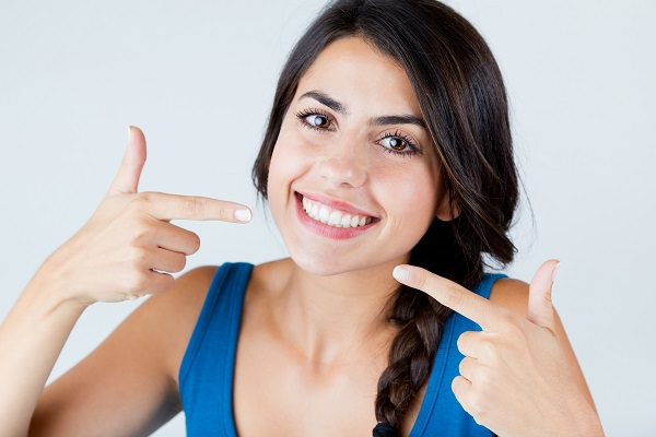 Young woman smiling and pointing at her flawless teeth after porcelain veneer placement